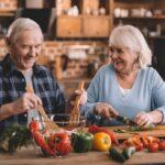 Smiling senior man and woman preparing vegetables to eat