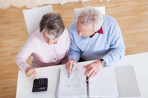Senior Couple Calculating Budget At Home