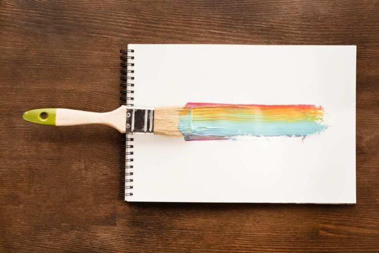 Notepad-on-wood-table-paintbrush-creating-a-rainbow-streak