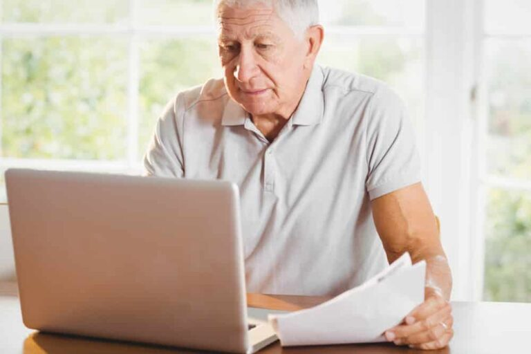 Senior-man-holding-papers-and-looking-at-laptop