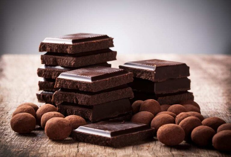 Squares-of-dark-chocolate-in-stacks-surrounded-by-chocolate-covered-nuts