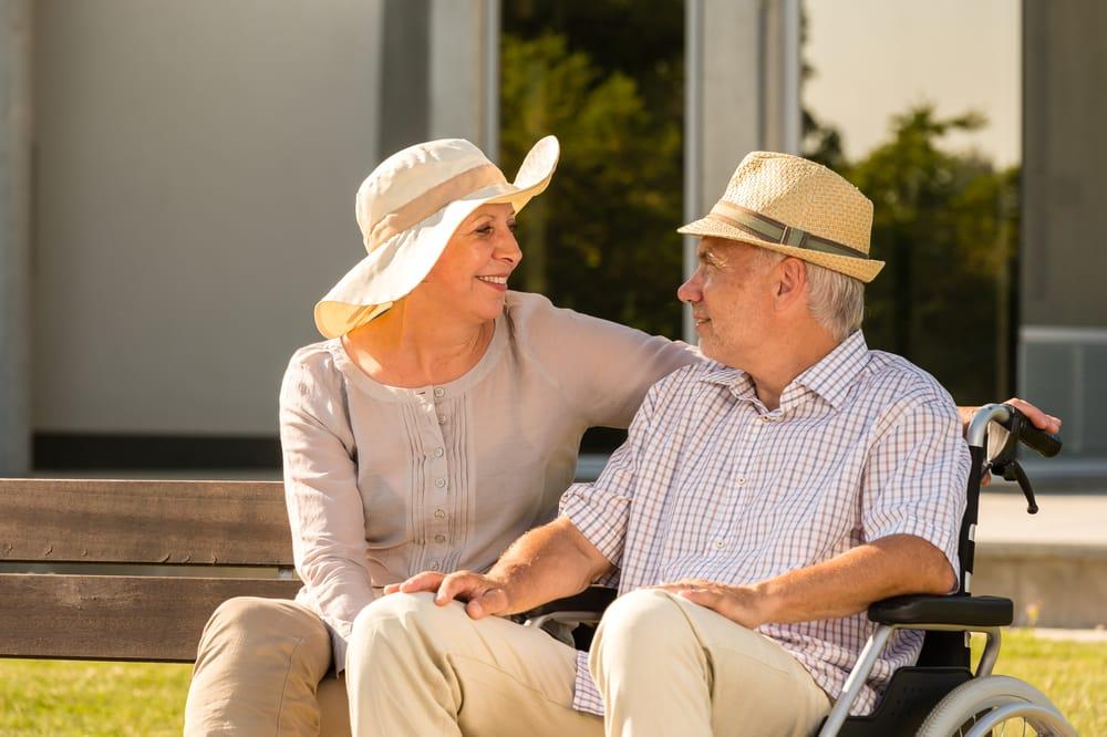Senior man and woman talking outdoors wearing sunhats
